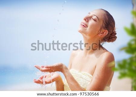 woman on the beach having tropical shower, bali - stock photo