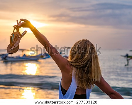 Woman on the beach in Bali Indonesia holding her sandals at sunset #297303128