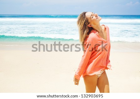 woman on the beach in pink shirt