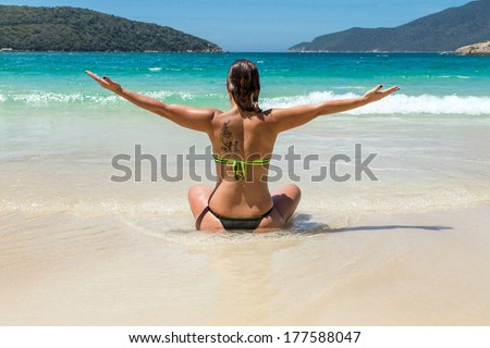 Woman on the beach looking out to sea and meditating.