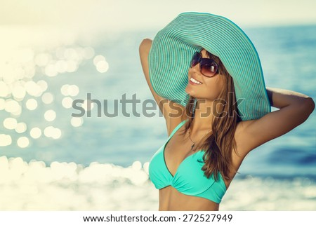 Woman on the beach wearing a hat. Young sexy woman relaxing and smiling on a beach near a blue sunny sea. Eternal summer concept. #272527949