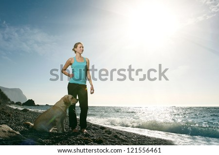 woman on the beach with a dog labrador retriever on a sunny day