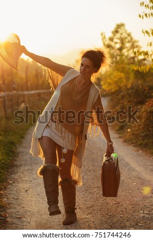 Woman on the contry side road,with suitcase
