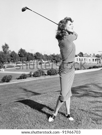 Woman on the driving range swinging a golf club