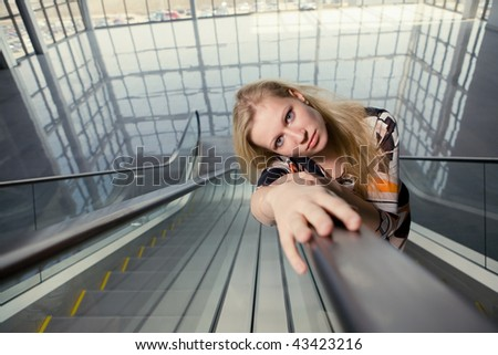 woman on the escalator with her hands on the handrail and laid her head on hands