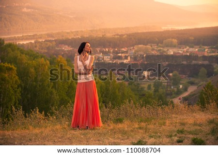 Woman on the hill enjoying beautiful summer sunset.