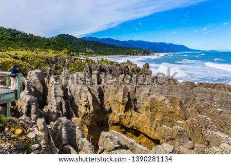 """Woman on the observation deck takes pictures of rocks and ocean surf. New Zealand. Stone flat """"pancakes"""", stacked on top of each other. The concept of ecological, active and photo tourism"""