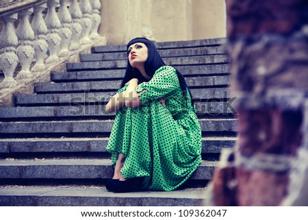 Woman on the old stairs in green dress