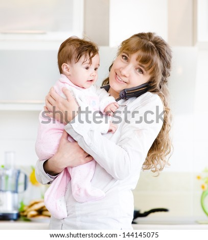 woman on the phone while holding her baby in her arms in the kitchen