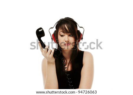 woman on the phone with ear defenders on so she cant hear what the person on the other end of the phone has to say - stock photo