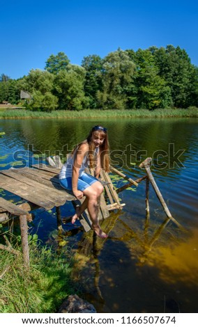 Woman on the sea, the lake. Cute woman on a half-ruined wooden bridge over blue water on a sunny day #1166507674