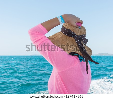 Woman on the ship in a hat looking at sea
