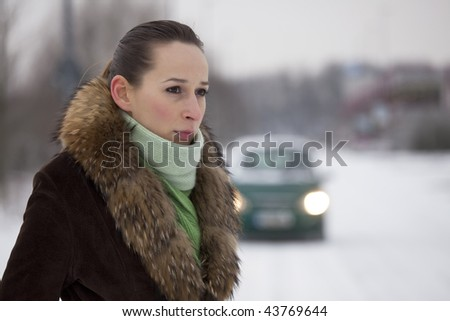 woman on the snowy road - car in background