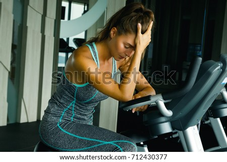 Woman on the stationary bike with overtraining symptoms