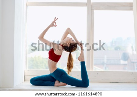 Stock Photo woman on the windowsill doing yoga fitness asana