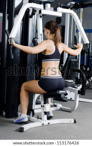 Woman on training apparatus in sports club