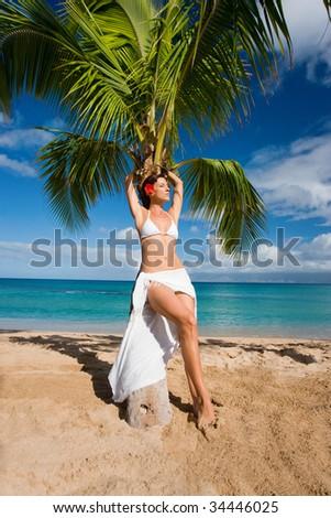 woman on tropical beach leaning on palm tree in white sarong and bikini relaxing in sun maui, hawaii - stock photo