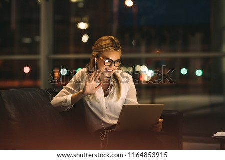 Woman on video call using a digital tablet sitting in office lobby. Smiling businesswoman late at night in office making gestures on a video call.