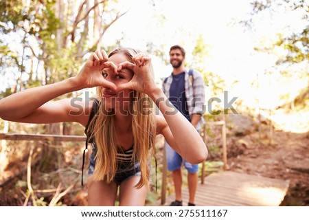 Woman On Walk With Man Making Heart Shape At Camera