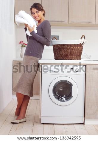 woman on washing machine in kitchen Foto stock ©