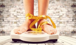 Woman on weight scales and measuring tape