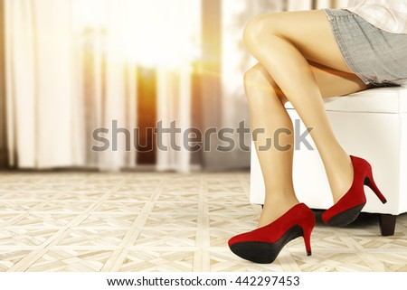 woman on white sofa and red heels