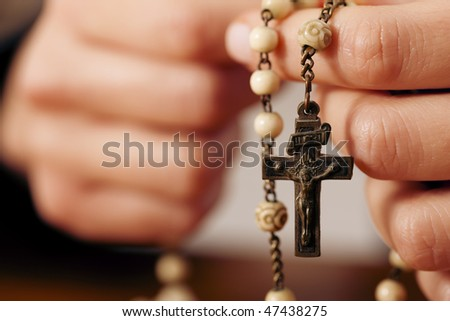 Woman (only closeup of hands to be seen) with rosary sending a prayer to God, the dark setting suggests she is sad or lonely