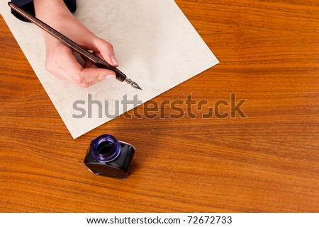 Woman (only hand to be seen) writing a letter on paper with a pen and ink, in the foreground she has an ink pot