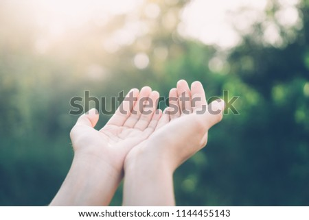 Woman open hand up to sunset sky and green blur leaf bokeh sun light abstract background. Vintage tone filter effect color style.