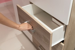 Woman open shelf, pull open drawer wooden in cabinet.