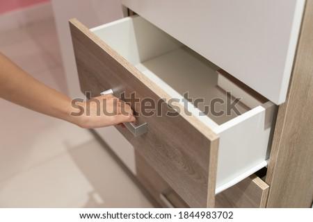 Woman open shelf, pull open drawer wooden in cabinet. Foto stock ©