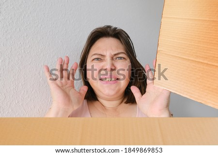 woman opened a cardboard box with an ordered product and emotionally reacts to its contents, the concept of a postal item, a package, buying goods online, surprises 商業照片 ©