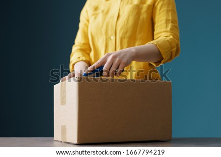 Woman opening a delivery box using a cutter Stockfoto ©