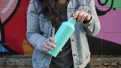 Woman opening a stainless steel water bottle. Her head is out of frame, she's wearing a jean jacket and behind her is a graffiti wall.