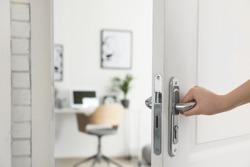 Woman opening door to stylish room, closeup. Interior design
