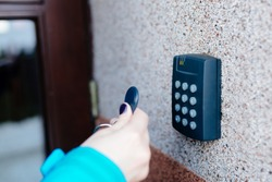 Woman opening house doors with electronic remote transmitter