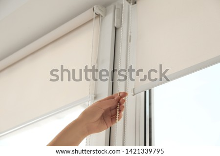Woman opening modern roll blinds on window in room, closeup #1421339795