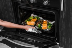 woman opens the oven. hand on the oven door. baked trout in the oven. woman is cooking dinner in the oven with baked salmon.
