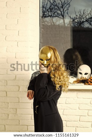 Woman or girl cover face with golden mask with long blond hair at window. Carnival, masquerade, masque party, holiday celebration. Decoration, amusement, protection, disguise, pretense concept.