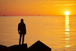 Woman or man standing on rock looking straight. Nature and beauty concept. Orange sundown. Girl silhouette at sunset