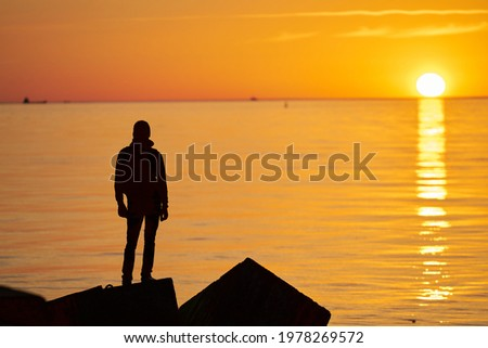Woman or man standing on rock looking straight. Nature and beauty concept. Orange sundown. Girl silhouette at sunset Stock fotó ©