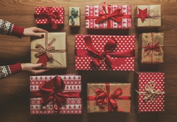 Woman organising beautifuly wrapped vintage christmas presents on wooden background, image with haze, view from above