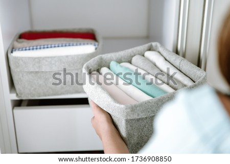 Woman organizing clothes in wardrobe, putting shirts in boxes, baskets into shelves and drawer. Concept of minimalism lifestyle and japanese t-shirt folding system. Tidy up closet Foto stock ©