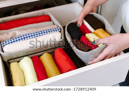 Woman organizing clothes in wardrobe, putting stuff in boxes, baskets into shelves and drawer. Concept of minimalism lifestyle and japanese t-shirt folding system. Tidy up closet Stockfoto ©