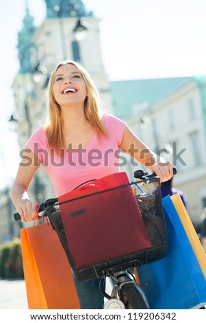 Woman outdoors on bicycle with shopping bags