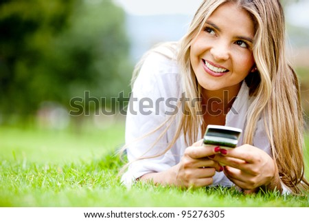 Woman outdoors texting on her mobile phone