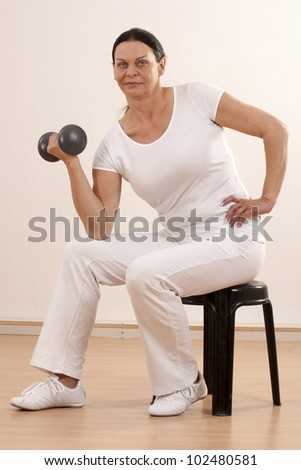 Woman over forty, sitting on a training exercise /Frau mit Hantel