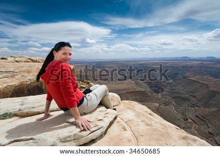 Woman overlooking Goosenecks State Park and Monument Valley, Utah, from Muley Point