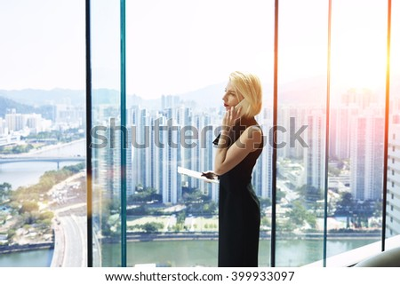 Woman owner of successful enterprise with touch pad in hand having serious conversation with manager about the loss of new clients, while is standing in skyscraper office interior during business trip