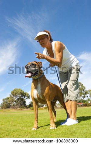Woman owner with friend and big pet boxer bull dog in park, alert and training, exercising, isolated with blue sky as background and copy space.